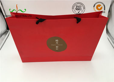 China Red Coated Paper Printed Gift Bags With Handles For Cosmetics Packaging supplier